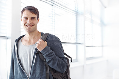 Buy stock photo Handsome young student standing with a backpack slung over his shouder - copyspace