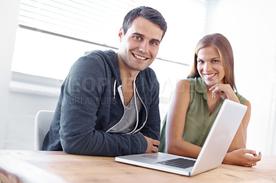 Buy stock photo Young male and female students sitting at a laptop and smiling at the camera - portrait