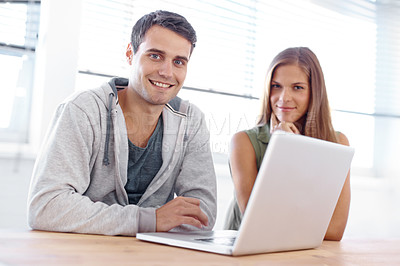 Buy stock photo Two male and female students sitting at a laptop and smiling at the camera - portrait