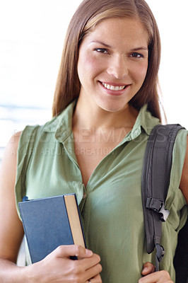 Buy stock photo Closeup of a lovely young student holding a book with a backpack slung over her shoulder - portrait