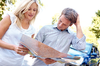 Buy stock photo A mature couple looking at a map in confusion while out on a walk