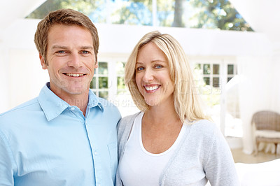 Buy stock photo A loving mature couple standing in their lounge together and smiling
