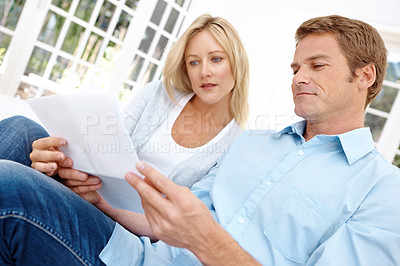 Buy stock photo A mature couple going over a bill while sitting in their lounge together