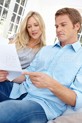 Buy stock photo A mature couple going over a financial document while sitting in the lounge together