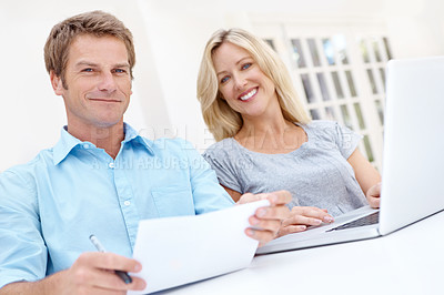 Buy stock photo A mature couple doing their monthly budget together using a laptop