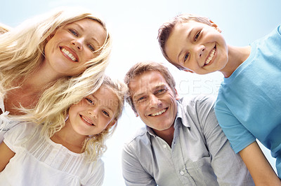 Buy stock photo Portrait of a smiling family looking down at the camera