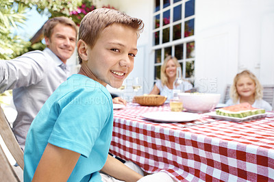 Buy stock photo Portrait of a boy adn his family sitting down to a meal outside