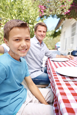 Buy stock photo Portrait of a son smiling at the camera while sitting at a table outside with a plate infront of him and his father in the background