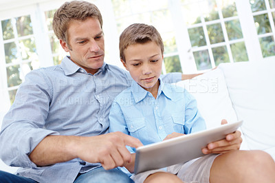 Buy stock photo A son and father sitting on the couch looking at a digital tablet