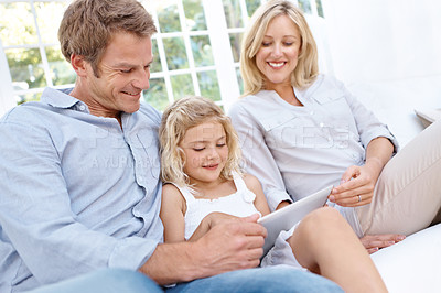 Buy stock photo A happy family sitting on a couch looking at a digital tablet and smiling