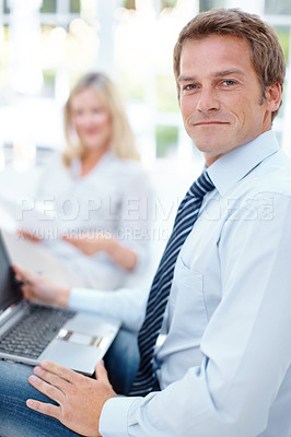 Buy stock photo Portrait of a smiling business man with a laptop on his lap and a blurred woman in the background