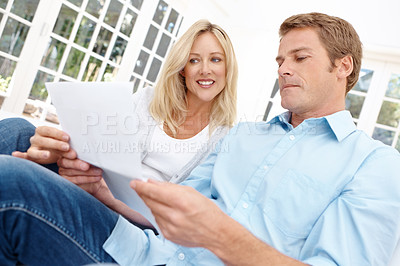 Buy stock photo A man and a woman look at a document together