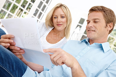Buy stock photo Shot of a young couple looking at some paperwork while sitting on the sofa
