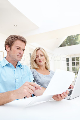 Buy stock photo Man and woman looking over a document with a laptop in front of them