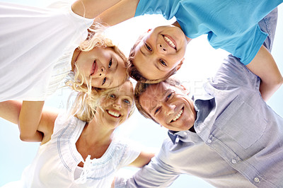 Buy stock photo Low-angle view of a cute family huddle with their arms around each other's shoulders