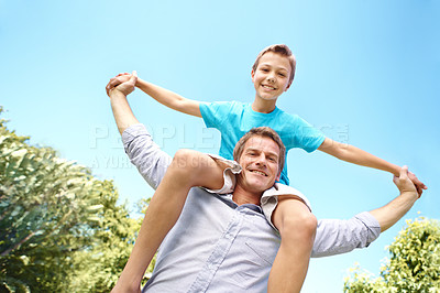 Buy stock photo Handsome father carrying his young son on his shoulders