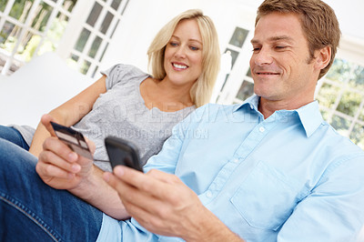 Buy stock photo Mature couple sitting on the sofa together and using a mobile phone and a credit card together