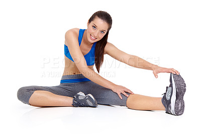 Buy stock photo A pretty young woman sitting on the floor and stretching her leg out - Isolated