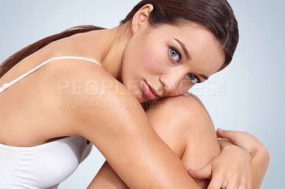 Buy stock photo A stunning young woman hugging her legs and looking at you - studio shot
