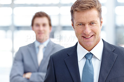 Buy stock photo A mature businessman smiling at you confidently while a colleague stands in the background
