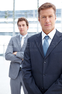 Buy stock photo An experienced executive standing with a colleague blurred in the background