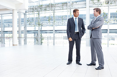 Buy stock photo Two businessmen having a lively discussion in the lobby of their office - Copyspace
