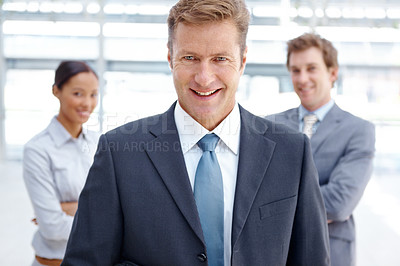Buy stock photo An experienced business manager standing with his colleagues blurred in the background