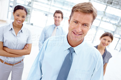 Buy stock photo A smiling business manager standing with his business team behind him