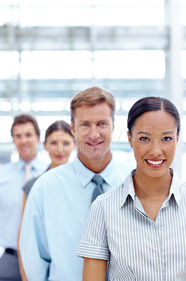 Buy stock photo A pretty african-american businesswoman standing in front of her team and smiling