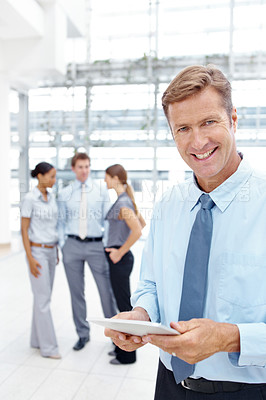 Buy stock photo A mature businessman working on his digital tablet while his colleagues stand in the background