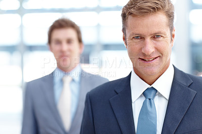 Buy stock photo A handome buisnessman smiling at the camera with his partner in the background