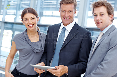 Buy stock photo Three attractive businesspeople standing with a digital tablet