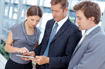 Buy stock photo Three attractive businesspeople working on a digital tablet