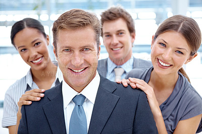 Buy stock photo A team of businesspeople standing happily behind their boss