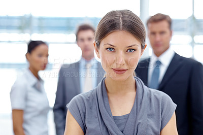 Buy stock photo A gorgeous young businesswoman looking at the camera with a group of colleagues in the background