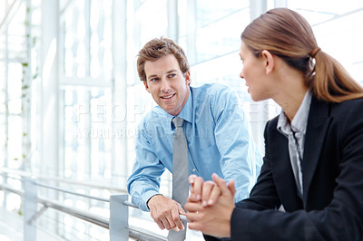 Buy stock photo Two colleagues discussing business while standing in the hallway