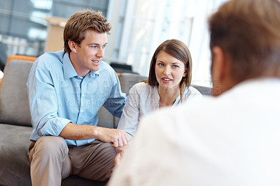 Buy stock photo A couple listening to the advice of a financial advisor