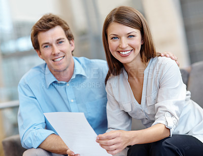 Buy stock photo A couple smiling at the camera while holding a document