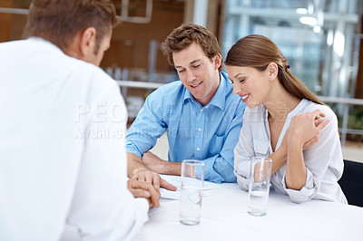 Buy stock photo A young couple going over details in a contract with their financial advisor