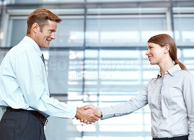Buy stock photo A handsome businessman shaking hands with a young businesswoman