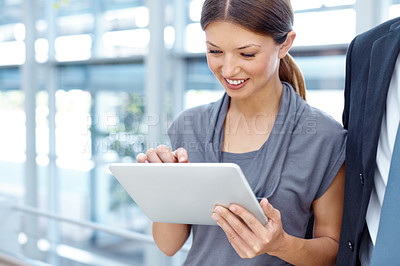 Buy stock photo Cropped view of a pretty young businesswoman using a digital tablet alongside a coworker
