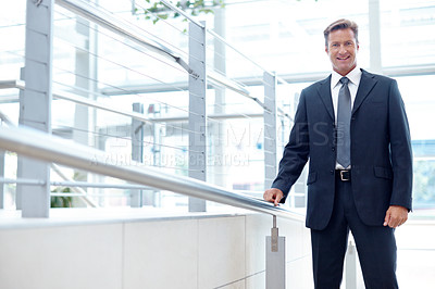Buy stock photo Mature businessman smiling while standing indoors alongside copyspace