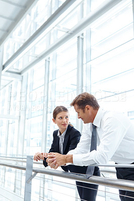Buy stock photo Two businesspeople having a discussion alongside a railing