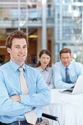 Buy stock photo Young businessman sitting with his arms folded while his coworkers look on