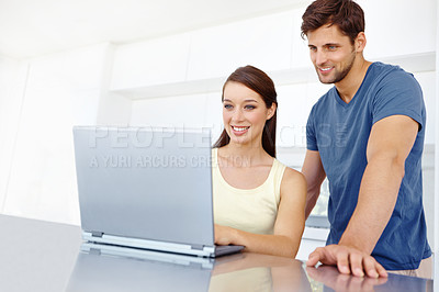 Buy stock photo A happy couple looking at their laptop