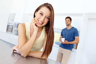 Buy stock photo Pretty woman leaning on her kitchen counter and smiling with her boyfriend in the background