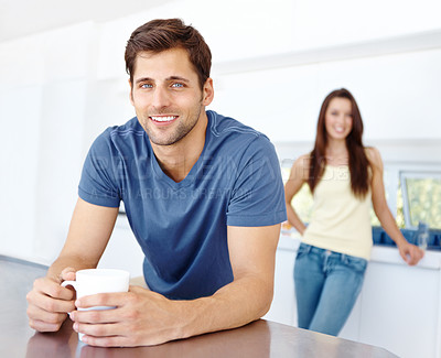 Buy stock photo A handsome man leaning on his kitchen counter with a hot beverage with a woman in the background