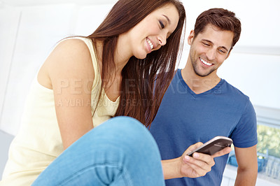 Buy stock photo A happy couple looking at their new cell phone