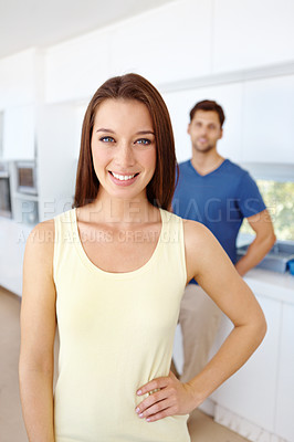 Buy stock photo Pretty female posing in her kitchen with her boyfriend in the background