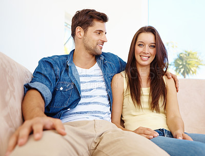 Buy stock photo A happy couple sitting on the couch with the male looking at his girlfriend lovingly